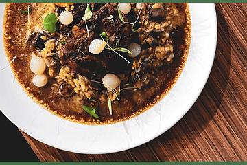 Guiso de arroz con carne y longaniza de emú, con variedad verduras y hortalizas, con crema trufada